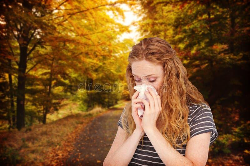 Image composée de la femme blonde malade soufflant son nez image stock
