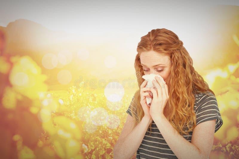 Image composée de la femme blonde malade soufflant son nez image libre de droits