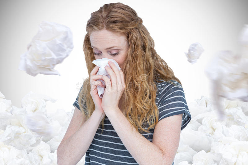 Image composée de la femme blonde malade soufflant son nez photographie stock libre de droits