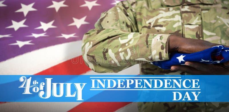 Image composée de la mi section du soldat tenant le drapeau américain photos stock