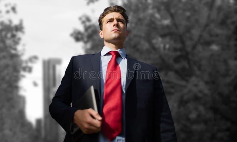 Image composée de la vue d'angle faible de l'homme d'affaires tenant le comprimé numérique image stock