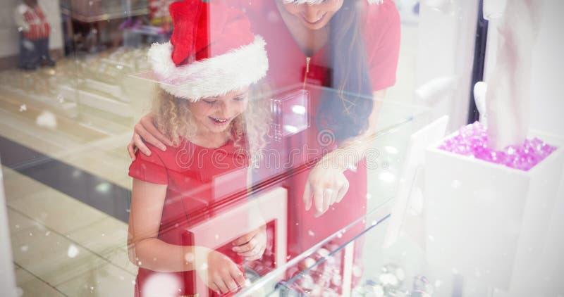Image composée de mère et de fille dans le vêtement de Noël regardant l'affichage de montre-bracelet photos libres de droits