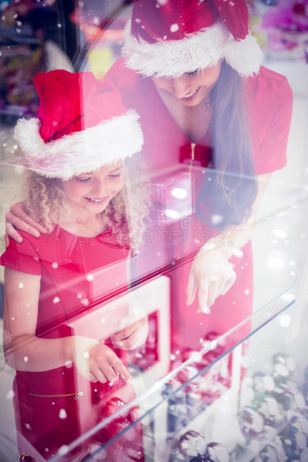 Image composée de mère et de fille dans le vêtement de Noël regardant l'affichage de montre-bracelet photographie stock libre de droits