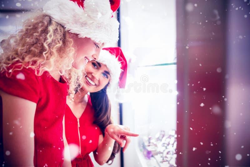 Image composée de mère et de fille gaies dans le vêtement de Noël regardant l'affichage de montre-bracelet image stock