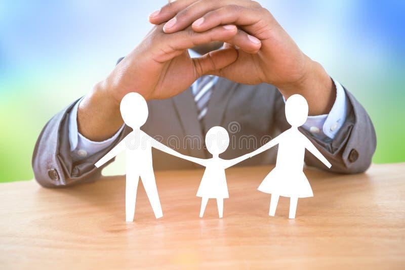 Image composée de main protégeant une famille en papier photo libre de droits