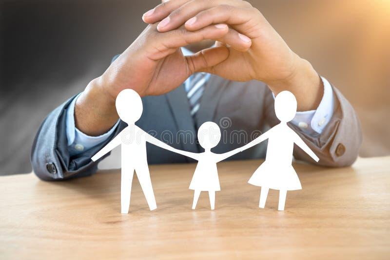 Image composée de main protégeant une famille en papier photos libres de droits