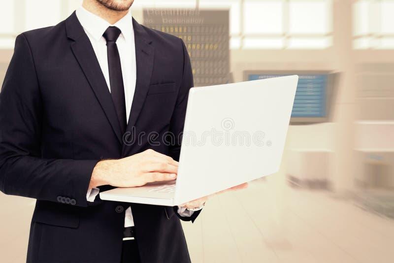 Image composée de mi section d'un homme d'affaires utilisant l'ordinateur portable photo stock