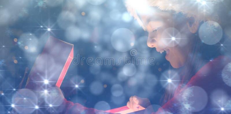 Image composée de petite fille ouvrant un cadeau magique de Noël photos stock