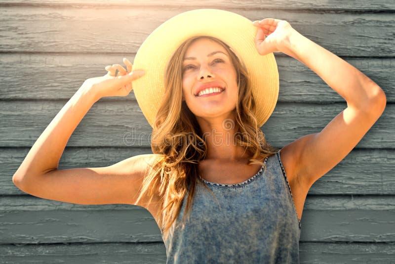 Image composée de portrait d'une femme touchant son chapeau de paille photo libre de droits