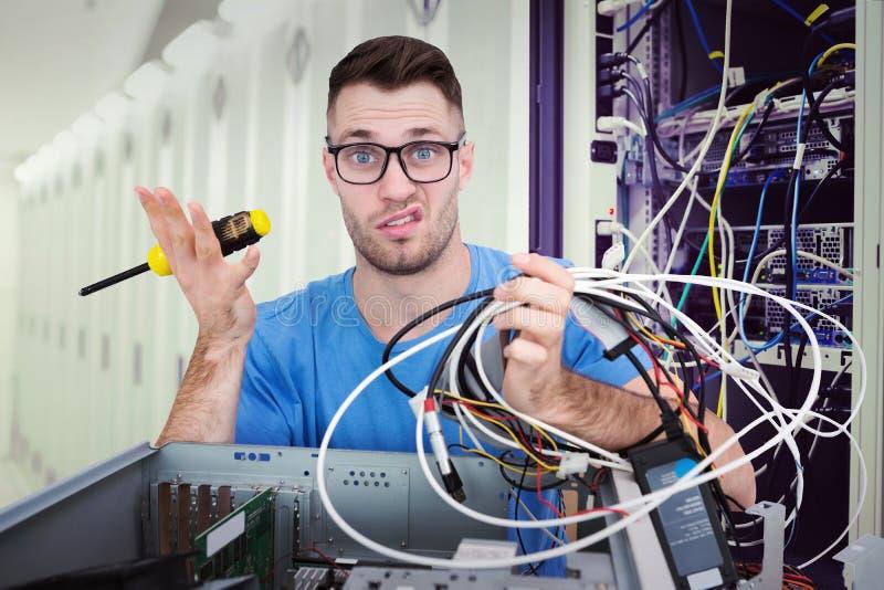 Image composée de portrait de confus il professionnel avec le tournevis et les câbles devant l'ope images libres de droits