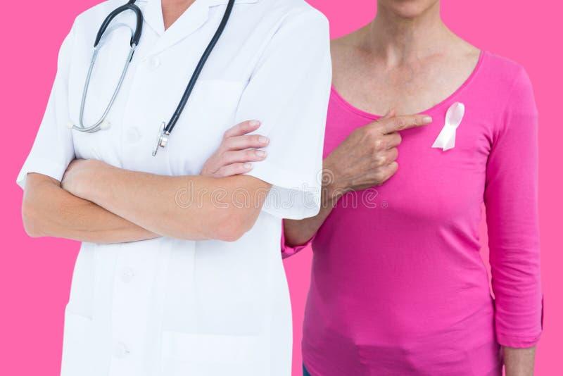 Image composée de section médiane des mains debout de docteur féminin pliées photographie stock libre de droits