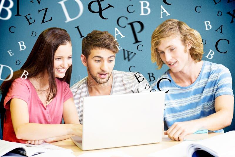 Image composée des étudiants universitaires à l'aide de l'ordinateur portable dans la bibliothèque images stock