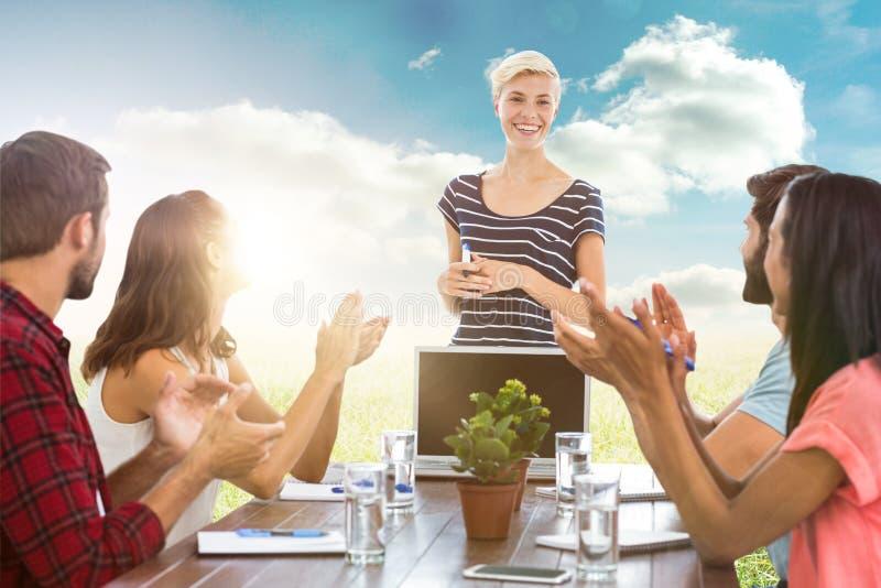 Image composée des collègues battant des mains lors d'une réunion images stock