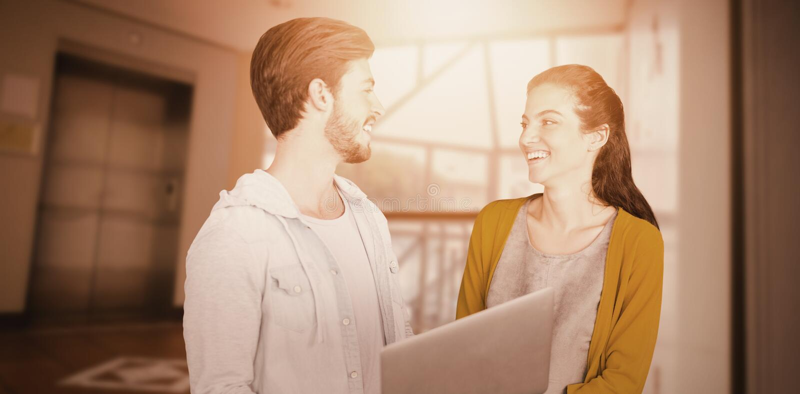 Image composée des collègues d'affaires regardant l'un l'autre tout en à l'aide d'un ordinateur portable photos libres de droits