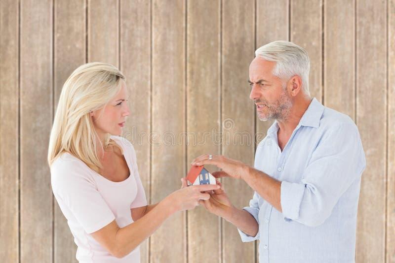 Image composée des couples combattant au-dessus de la maison modèle miniature images libres de droits