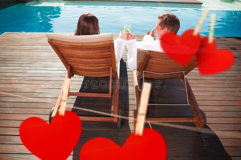 Image composée des couples grillant le champagne par la piscine images stock