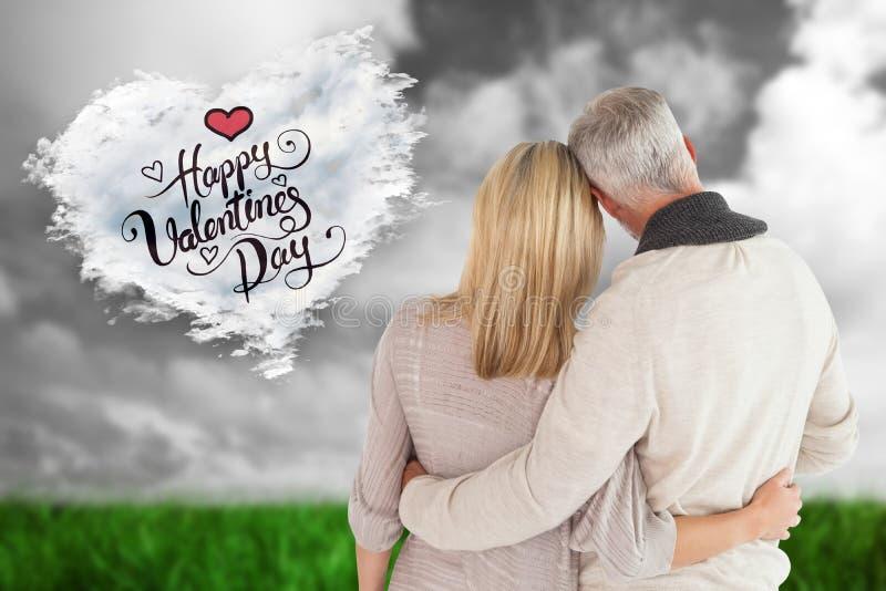 Image composée des couples heureux se tenant avec des bras autour images stock