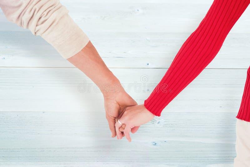 Image composée des couples partageant la vue arrière de mains photos libres de droits