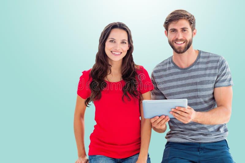 Image composée des couples posant avec le comprimé photographie stock