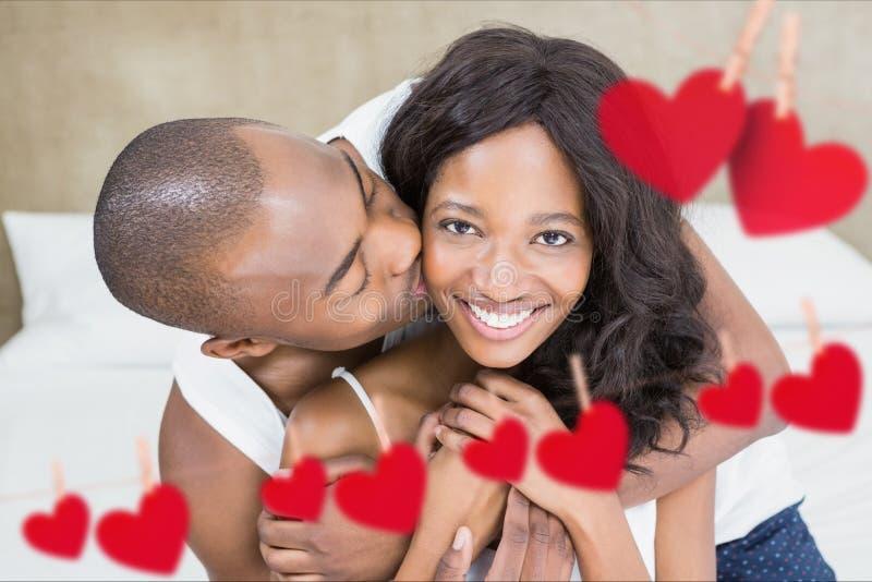 Image composée des couples romantiques sur le lit dans la chambre à coucher photos stock