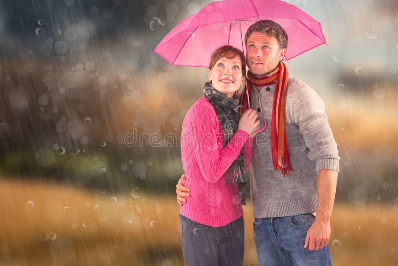 Image composée des couples se tenant sous un parapluie images libres de droits