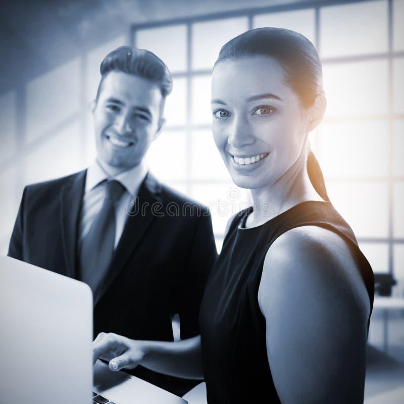 Image composée des gens d'affaires se tenant avec un ordinateur portable images stock