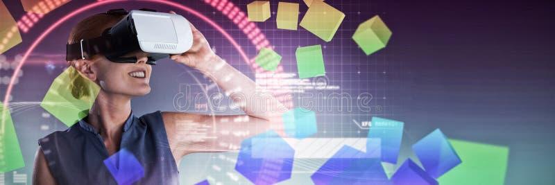 Image composée des verres de port de réalité virtuelle de jeune femme d'affaires heureuse image stock
