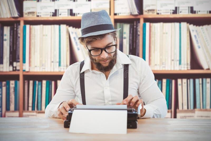 Image composée des verres et du chapeau de port d'oeil de hippie travaillant à la machine à écrire images stock