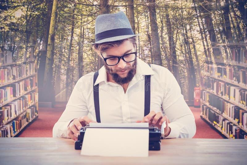 Image composée des verres et du chapeau de port d'oeil de hippie travaillant à la machine à écrire photos stock
