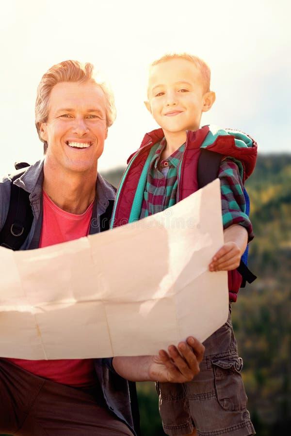 Image composée du père et de son fils regardant une carte photographie stock