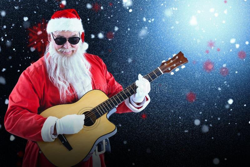 Image composée du père noël de sourire jouant la guitare tout en se tenant image stock