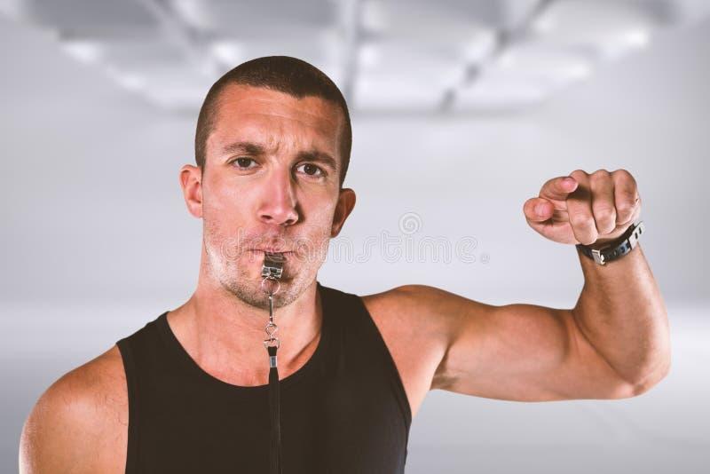 Image composée du portrait de l'entraîneur attentif soufflant le sien sifflement image libre de droits