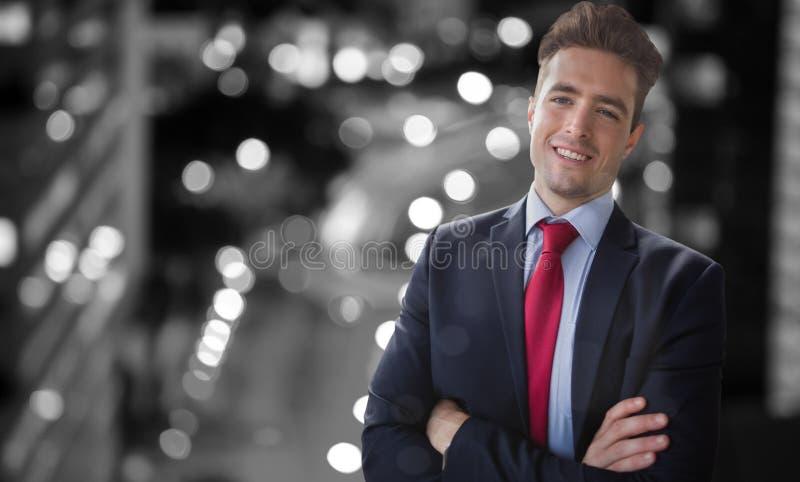 Image composée du portrait de l'homme d'affaires de sourire se tenant avec des bras croisés image libre de droits