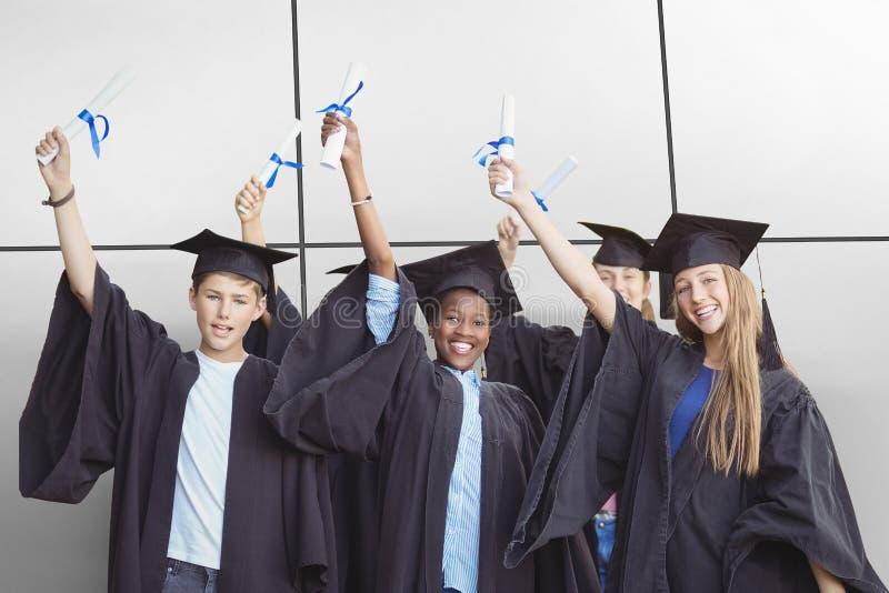 Image composée du portrait des étudiants de sourire tenant le degré photo libre de droits