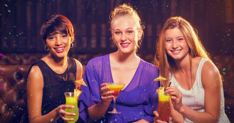 Image composée du portrait des amis tenant le verre du cocktail dans la barre image libre de droits