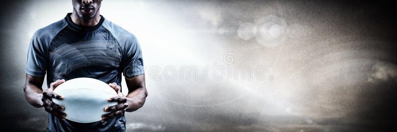 Image composée du portrait du sportif sérieux tenant la boule de rugby photo libre de droits