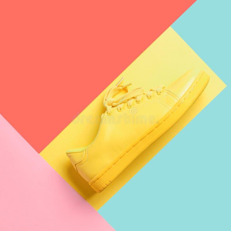 Image conceptuelle avec la chaussure jaune sur le fond à la mode photos stock