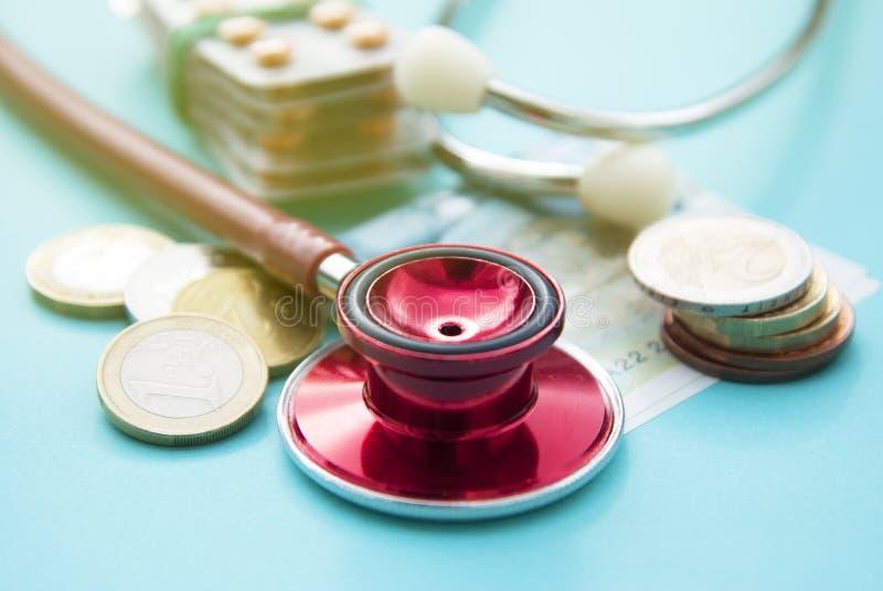 Image conceptuelle d'argent et de médecine Stéthoscope rouge sur une pile des pièces de monnaie, pilules au-dessus de fond bleu C photo libre de droits