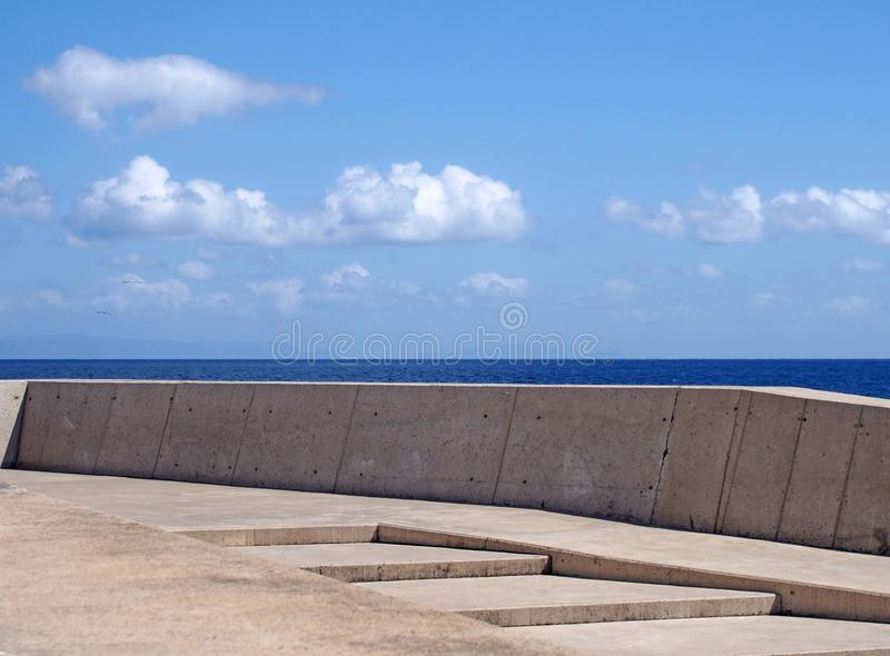 Image of a concrete sea wall with steps against a calm blue sea and sunlit blue sky. An image of a concrete sea wall with steps against a calm blue sea and royalty free stock images