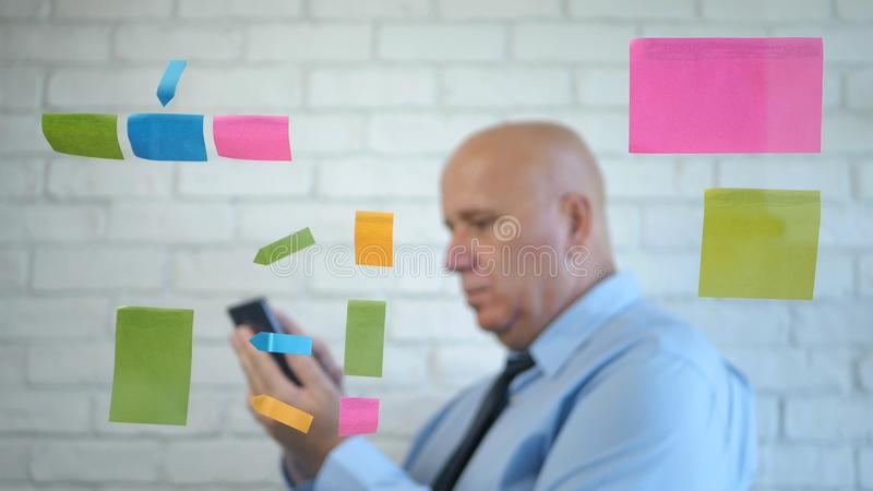 Confident Businessman Text Using a Cellphone in a Meeting royalty free stock images