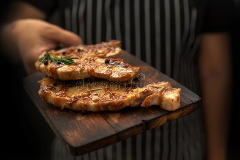 Image cooking on kitchen. Master Chef holding steak. Woman Chef stock photo