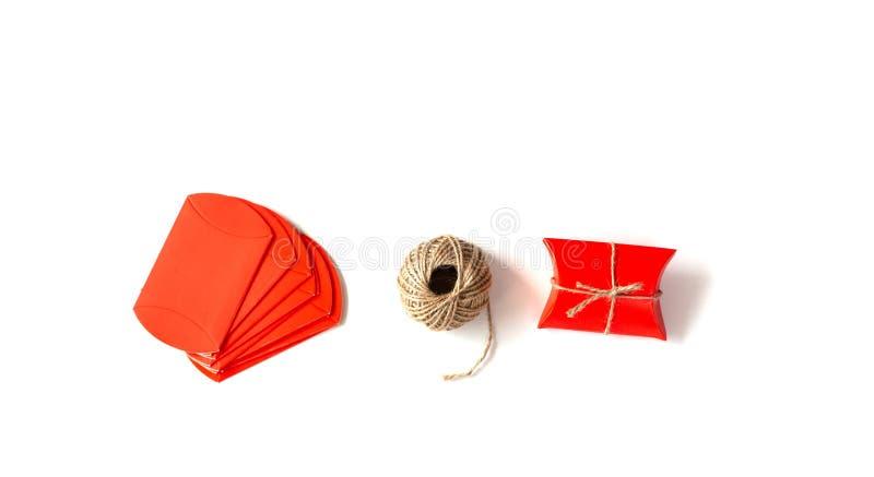 Image créative des paquets rouges et corde sur un fond blanc Cadeau fait main sur le fond blanc Concept de vacances images libres de droits