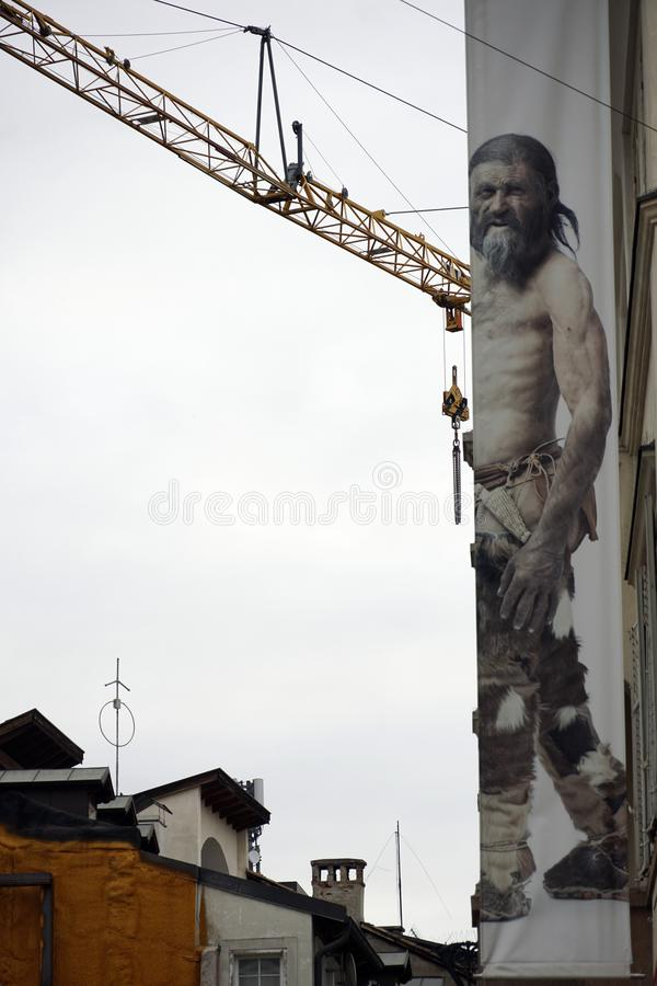 Image of a crane and a poster of ancient man Oetzi on the wall of Municipal Museum in Bolzano in Italy. South Tyrol Museum of Archaeology, Bolzano, South Tyrol royalty free stock image