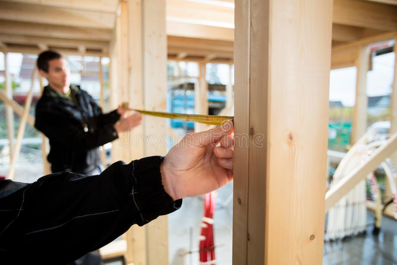 Image cultivée d'aide de Measuring Wood With de charpentier de collègue photos libres de droits