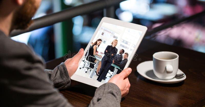 Image cultivée d'homme d'affaires assistant à la conférence téléphonique sur la tablette en café photos stock
