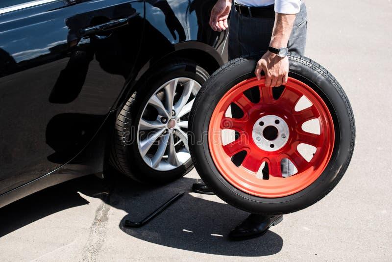 image cultivée d'homme d'affaires tenant le pneu pour le remplacement de roue images libres de droits