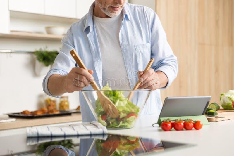 Image cultivée d'homme mûr faisant cuire la salade utilisant le comprimé photo libre de droits