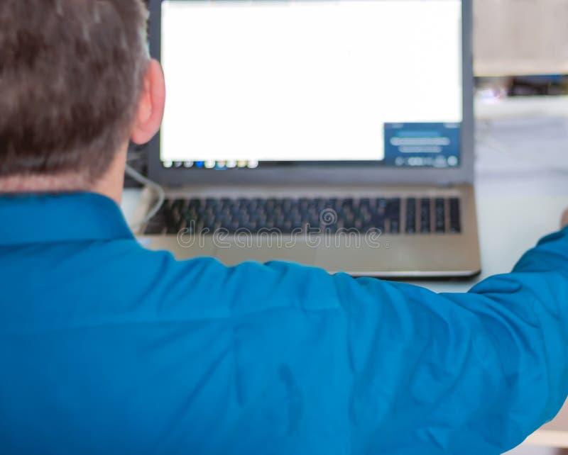 Image cultivée d'un homme travaillant sur sa vue arrière d'ordinateur portable photographie stock