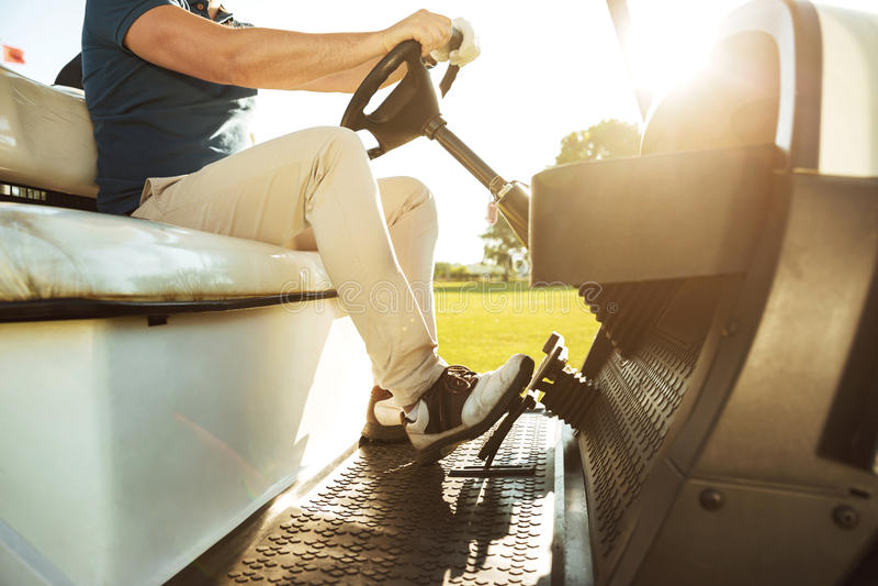 Image cultivée d'un jeune homme conduisant un chariot de golf photos stock