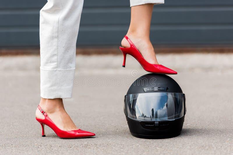 image cultivée de femme dans des talons hauts rouges mettant la jambe sur le casque de moto sur la rue photographie stock libre de droits